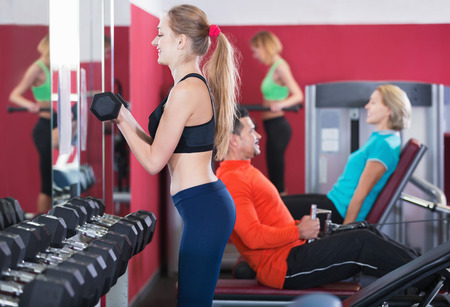 anaerobic: Positive glad smiling people  weightlifting training in modern health club