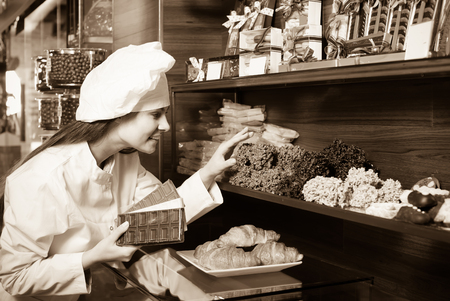 shopgirl: Happy young shopgirl posing with different delicious chocolate and confectionery at display Stock Photo