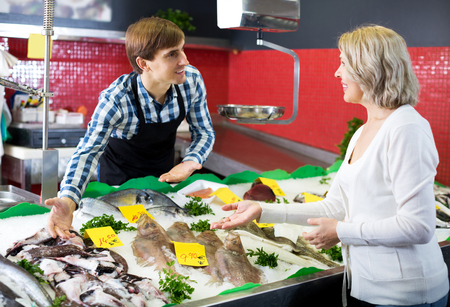 Smiling female pensioner purchasing chilled on ice fish in supermarket