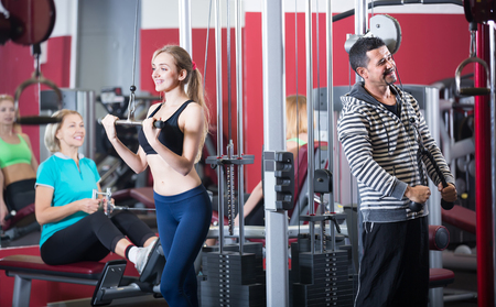 Smiling women and man having hard training on machines in fitness club