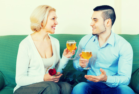 mismatch: Adult son congratulating senior mother and proposing a toast Stock Photo