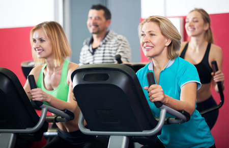 Smiling People Of Different Age Training On Exercise Bikes