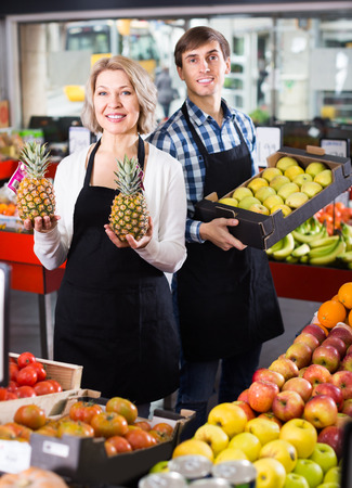 Smiling two workers  posing with fruits in local supermarket