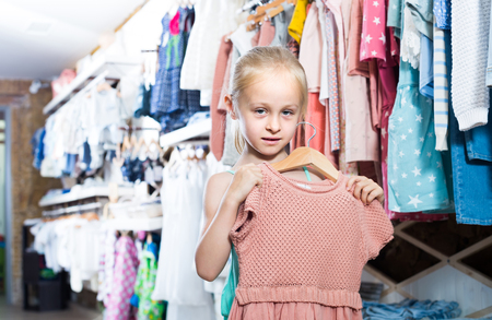 petticoat: Little positive girl holding new dress in hands in children clothes boutique