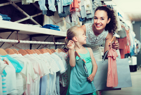 choosing clothes: Happy cheerful woman with small child choosing clothes in kids apparel boutique