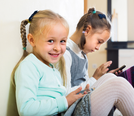 10s: Two small  sisters 10s and 7s playing with smartphones at home Stock Photo