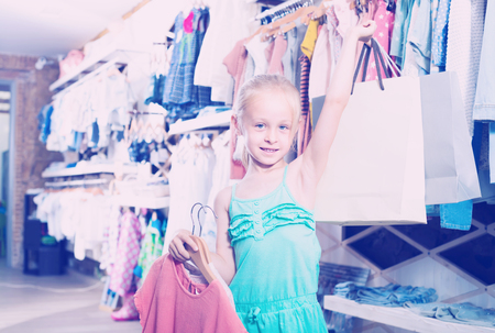 hapy: Hapy girl holding shopping bags in children clothes boutique