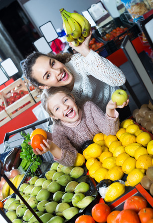 Laughing mother and daughter buying ripe fruits in supermarket