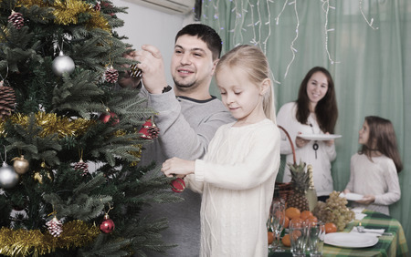 home decorating: Happy parents with children decorating Christmas tree at home. Focus on girl