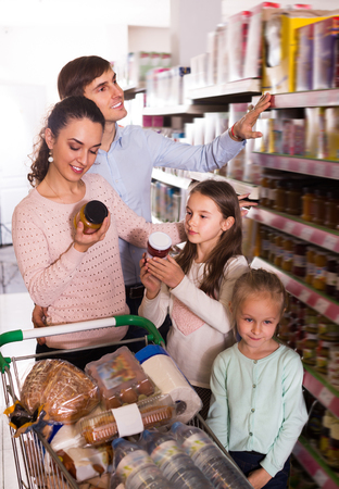 Customers with small kids  purchasing jam in hypermarket and smiling. Focus on woman Stock Photo