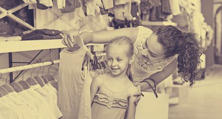 7880f0eb778 #62932213 - Mujer alegre joven con la pequeña muchacha que elige la ropa  azul en tienda de ropa de los niños