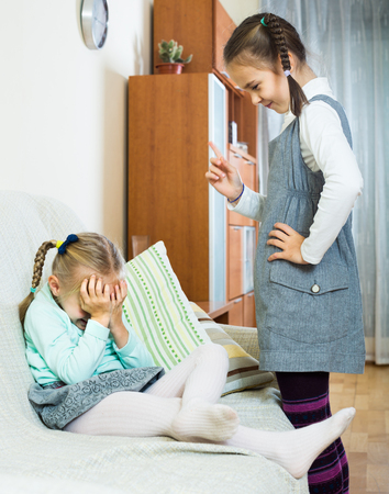 Serious spanish  girl lecturing little sister in domestic interior