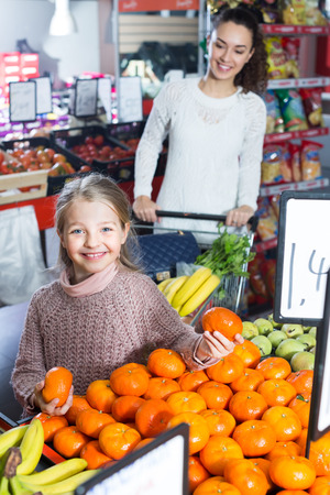 purchasers: Happy young woman and smiling little girl purchasing sweet tangerines at market
