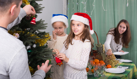 home decorating: Cheerful united family with kids decorating Christmas tree together at home. Focus on girl