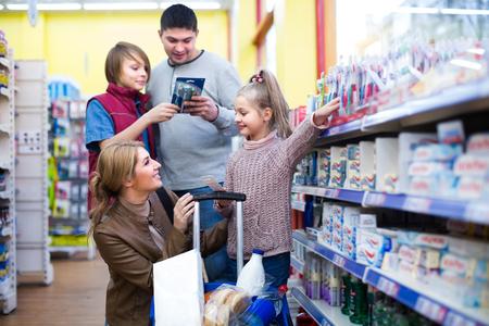 familia unida: familia unida con los ni�os la elecci�n de nuevos cepillos de dientes en el supermercado y sonriente. enfoque selectivo