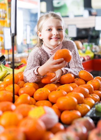 clementines: Portrait of cute little girl selecting ripe tangerines and smiling