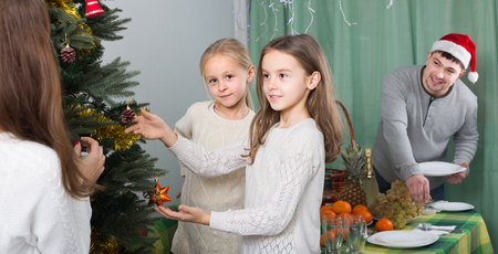 decorating christmas tree: cheerful parents with children decorating Christmas tree at home