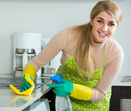 smiling russian blonde maid cleaning in domestic kitchen with sprayer Stock Photo