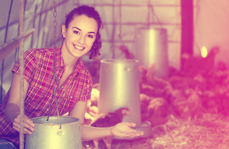 forage: happy young russian  woman farmer holding bucket with chicken forage in hen house