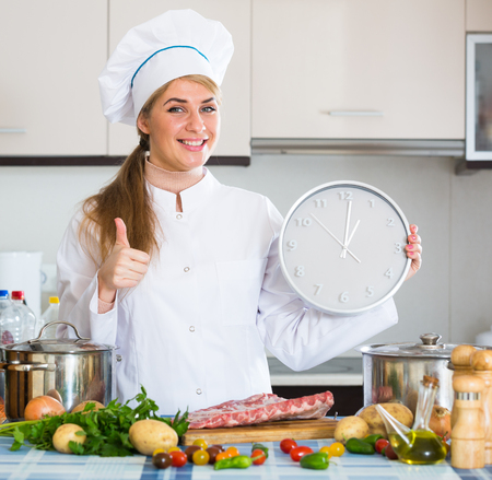 according: Positive female chef watching clock at kitchen according to recipe