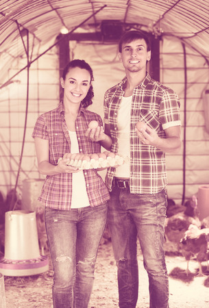 checking ingredients: Portrait of young man and woman farmer holding fresh eggs in carton in henhouse Stock Photo