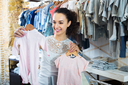 clothing shop: Woman buying baby sleep suit in kids in apparel shop