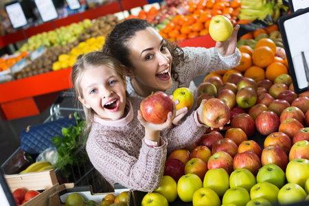 purchasers: Portrait of cheerful mother and little daughter buying ripe apples in supermarket . Focus on girl