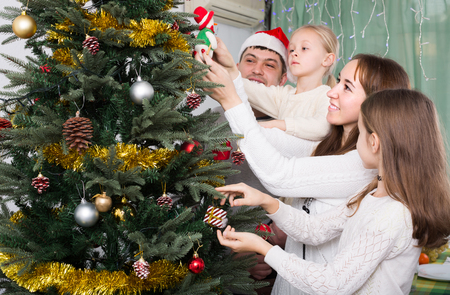 home decorating: Young united family of four decorating Christmas tree together at home. Focus on woman Stock Photo