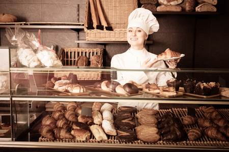 gladly: Positive girl cook gladly suggesting pastry in the cafeteria Stock Photo