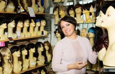 peruke: Positive brunette woman looking at periwigs in shop and smiling