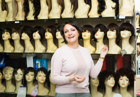 peruke: Smiling brunette female customer selecting natural hair wig in store Stock Photo