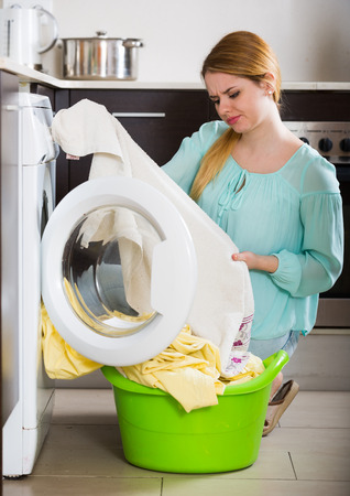 dirty sheet: Unhappy housewife with dirty bed linen near washing machine