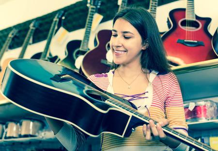 Brunette teenager girl choosing acoustic guitar in music instruments shop Stock Photo