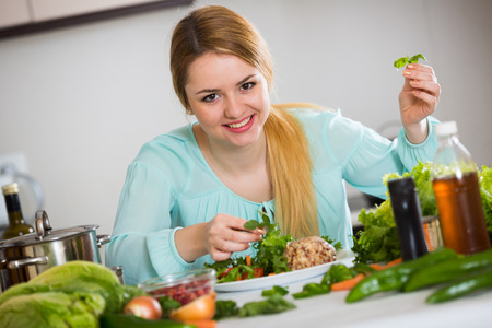 Pretty housewife decorating plate with vegetable salad and cheese