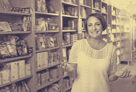 dietary supplements: Portrait of mature woman in biologically active dietary supplements store