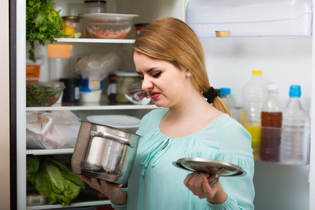 foul: upset american woman noticed foul smell of food from casserole Stock Photo