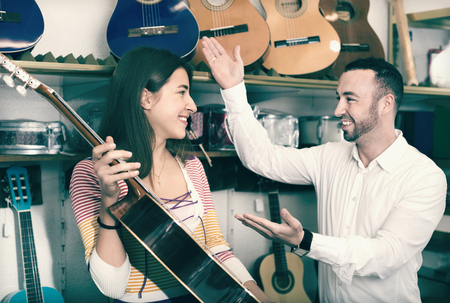 shopgirl: Friendly smiling  shopgirl helping male client to select guitar in shop Stock Photo