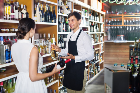 seller: Young man seller wearing uniform helping woman customer with a bottle of wine in wine house Stock Photo