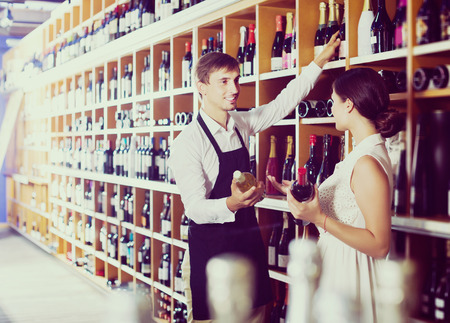 wine store: Smiling young seller man wearing apron helping to buy bottle of wine to woman customer in wine store