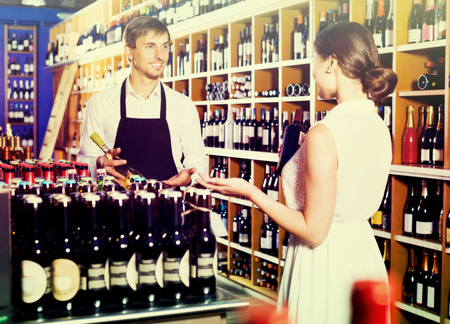 wine store: Glad seller man wearing apron helping to buy bottle of wine to woman customer in wine store Stock Photo