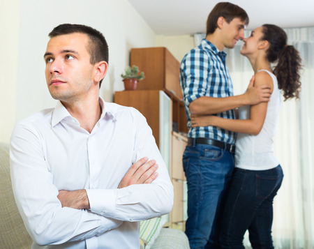 dishonesty: Young guy suffering from unrequited love indoors: woman chooses rival