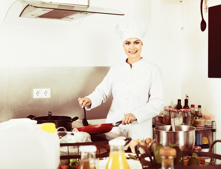 diligent: Cheerful positive diligent female young cook wearing uniform working on kitchen