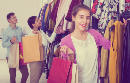 liked: Smiling female shopper chooses liked things in the boutique