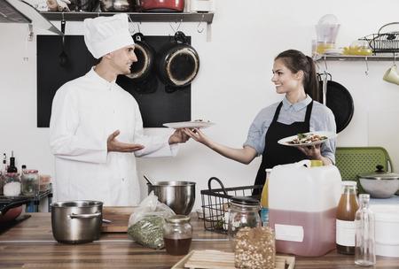 diligent: Portrait of diligent  smiling man cook giving to waitress ready to serve salad Foto de archivo