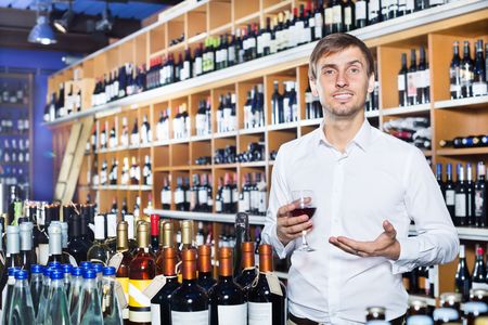 liquor: Young man customer holding glass of wine before buy it in a wine house Stock Photo