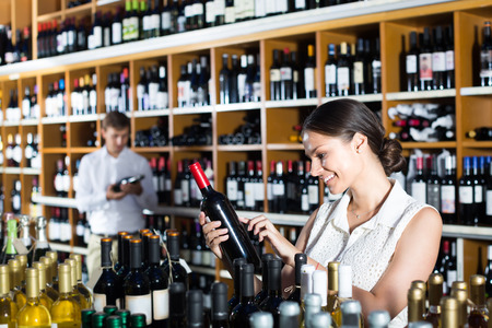 wine store: portrait of cheerful smiling young woman selecting bottle of wine in wine store