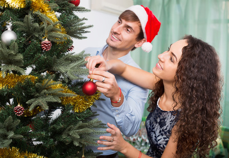 decorating christmas tree: Adult happy smiling couple decorating Christmas tree in home interior