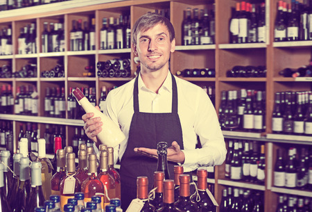 promoting: Positive seller man wearing apron promoting bottle of wine in wine store