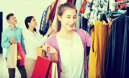 liked: Positive female shopper chooses liked things in the boutique