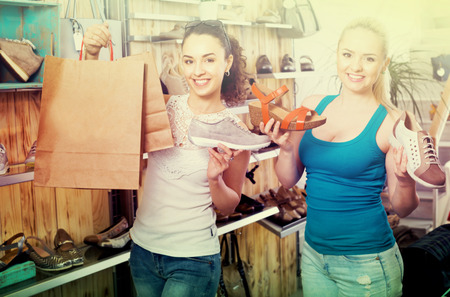 desires 25: Two glad young women shopping shoes and looking happy with a purchases. Focus on right person